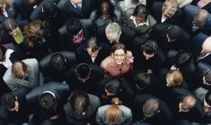 Businesswoman Looking up Surrounded by a Large Group of Business People