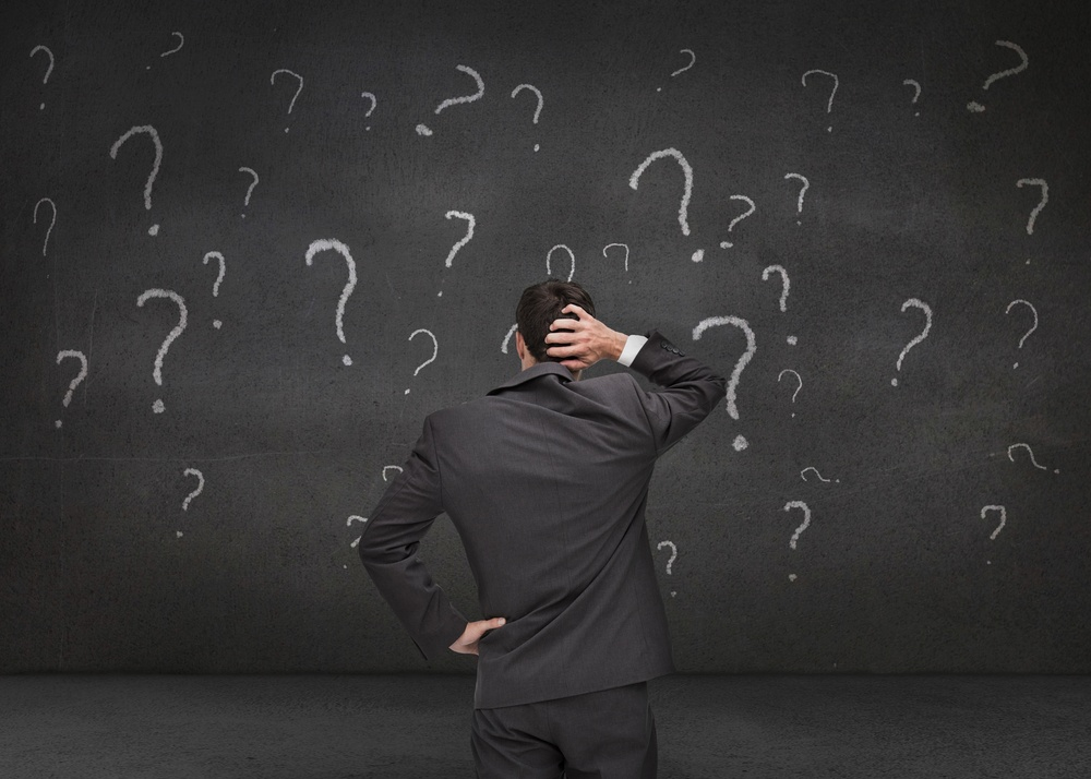 Rear view of doubtful businessman looking at question marks