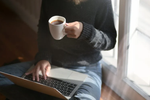 Girl working on laptop and drinking coffee