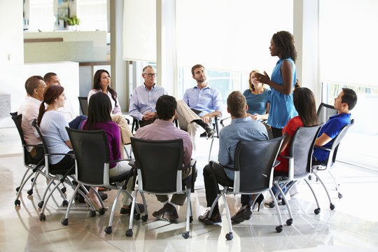 Business woman Addressing Multi-Cultural Office Staff Meeting