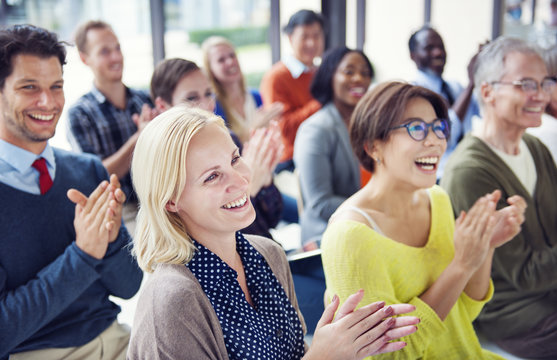 Group of people applauding in a meeting