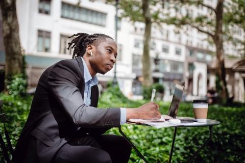 Man taking notes at desk outside