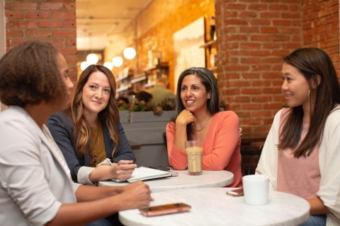four women sitting around a table talking