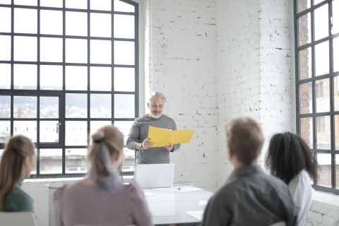Man with a folder standing in front of a small group