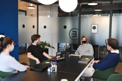 Coworkers sitting around a conference table with masks