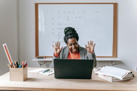 Teacher in classroom waving to her laptop screen