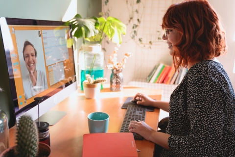 Woman smiling at an image of a coworker on her computer screen