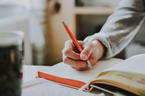 Hand holding a pen writing in a notebook