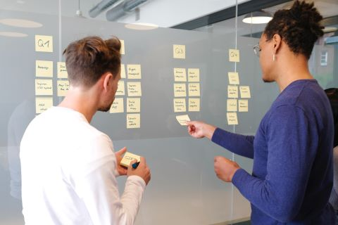Two people posting sticky notes on a wall