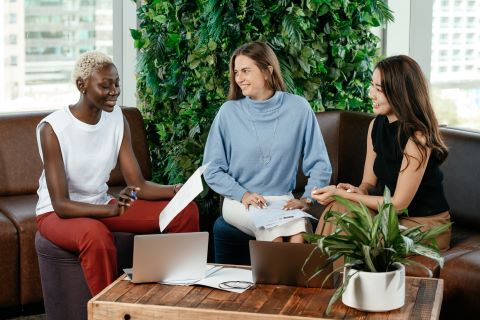 Three people sitting and smiling at each other in an office setting