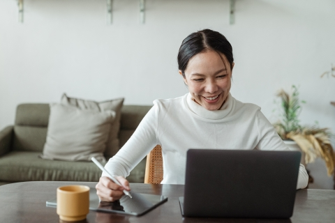 Woman smiling at her laptop while taking notes on a tablet