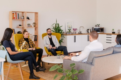 People talking while seated in a circle in an office environment