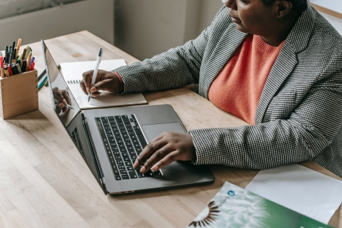 Woman with laptop writing in a notebook